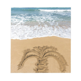 Drawing of palm tree on sandy beach notepad
