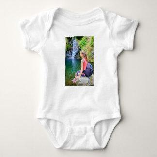 Dutch woman sitting on rock near waterfall baby bodysuit