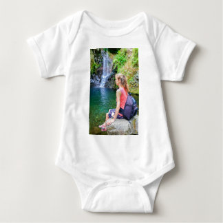 Dutch woman sitting on rock near waterfall baby bodysuit