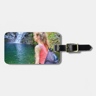 Dutch woman sitting on rock near waterfall luggage tag