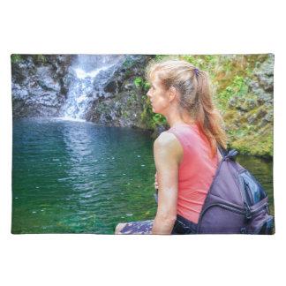 Dutch woman sitting on rock near waterfall placemat