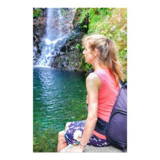 Dutch woman sitting on rock near waterfall stationery