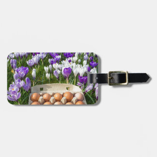 Egg box with chicken eggs in crocuses luggage tag