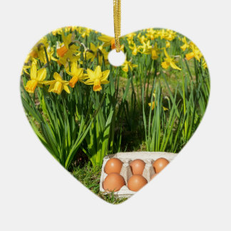 Eggs in box on grass with yellow daffodils ceramic ornament