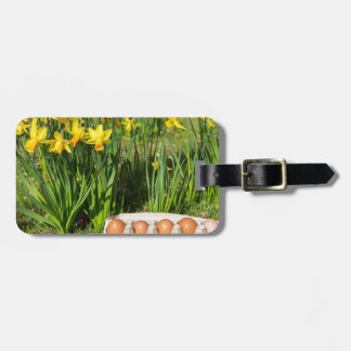 Eggs in box on grass with yellow daffodils luggage tag