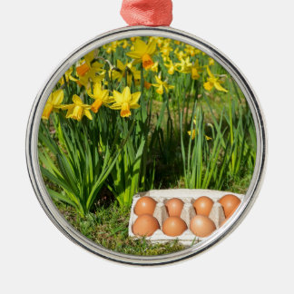 Eggs in box on grass with yellow daffodils Silver-Colored round decoration