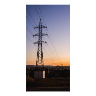Electricity tower close to an urban area against a card