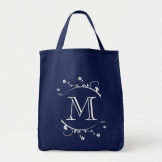 Elegante monograma y flores blancas en bolsa