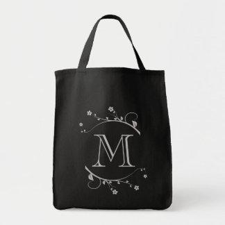 Elegante monograma y ramas en flor en bolsa