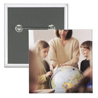 Elementary school teacher showing globe to 15 cm square badge