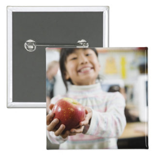 Elementary student holding an apple in her hand 15 cm square badge