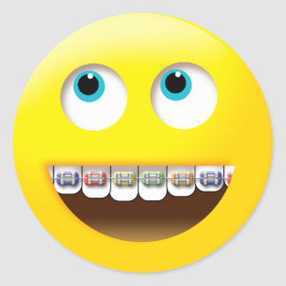 Emoji smiling with colorful braces round sticker
