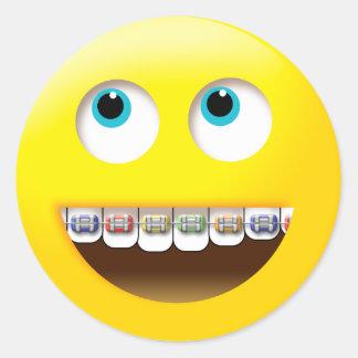 Emoji smiling with colorful braces round sticker