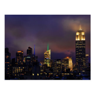 Empire State Building glows in clouds and fog Postcard