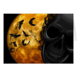 Evil skull and bats at full moon halloween card