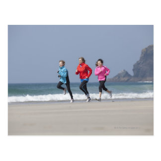 Family running together on beach postcard