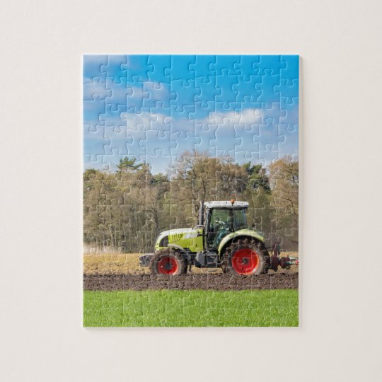 Farmer on tractor ploughing sandy soil in spring jigsaw puzzle