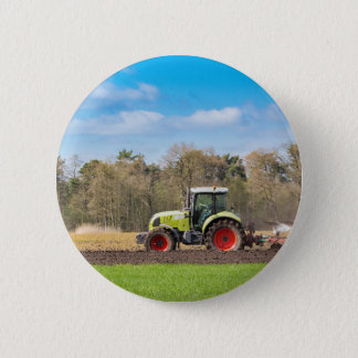 Farmer on tractor plowing sandy soil in spring 6 cm round badge