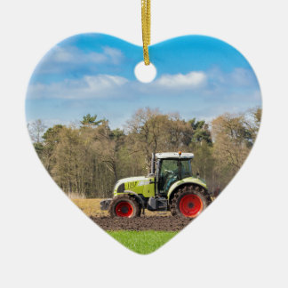 Farmer on tractor plowing sandy soil in spring ceramic heart decoration