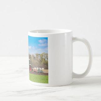 Farmer on tractor plowing sandy soil in spring coffee mug