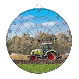 Farmer on tractor plowing sandy soil in spring dartboard