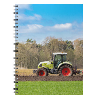 Farmer on tractor plowing sandy soil in spring notebook