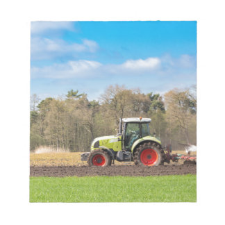 Farmer on tractor plowing sandy soil in spring notepad