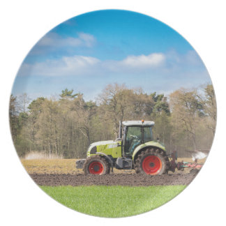 Farmer on tractor plowing sandy soil in spring party plates