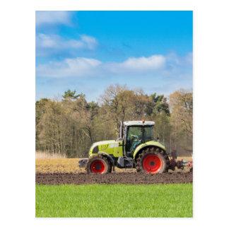 Farmer on tractor plowing sandy soil in spring postcard