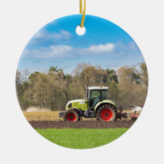 Farmer on tractor plowing sandy soil in spring round ceramic decoration