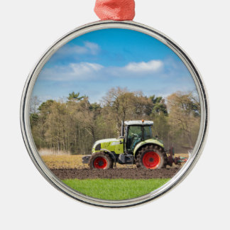 Farmer on tractor plowing sandy soil in spring Silver-Colored round decoration