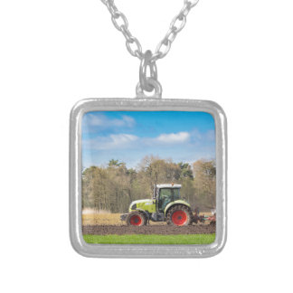 Farmer on tractor plowing sandy soil in spring silver plated necklace