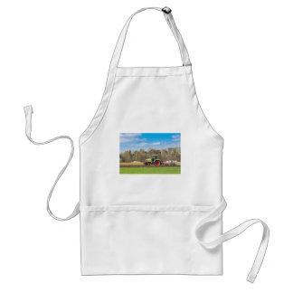 Farmer on tractor plowing sandy soil in spring standard apron