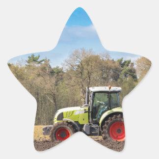 Farmer on tractor plowing sandy soil in spring star sticker