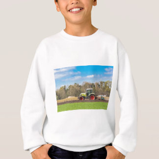Farmer on tractor plowing sandy soil in spring sweatshirt