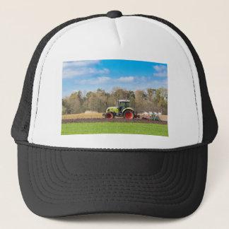 Farmer on tractor plowing sandy soil in spring trucker hat