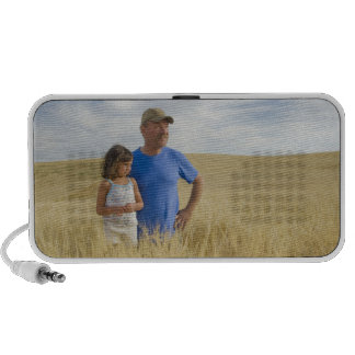 Farmer with a 5 year old girl in a field of notebook speakers