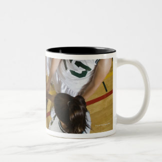 Female basketball team having group handshake, coffee mugs
