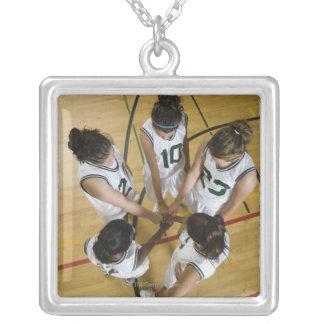 Female basketball team having group handshake, jewelry