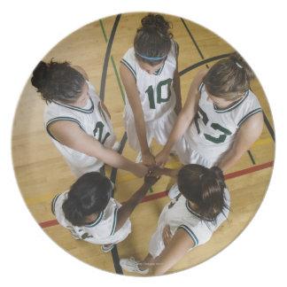 Female basketball team having group handshake, dinner plates