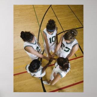 Female basketball team having group handshake poster