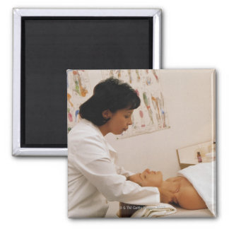 Female chiropractor massaging a patient square magnet