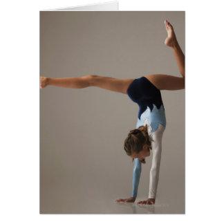 Female gymnast (12-13) performing handstand card