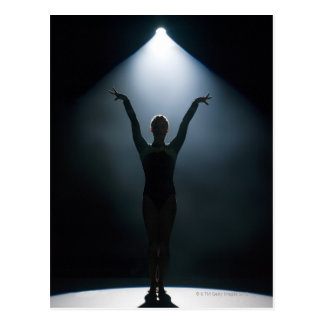 Female gymnast performing in spotlight, studio postcard