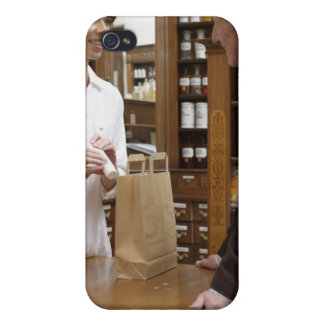 Female pharmacist advising customers iPhone 4 cases