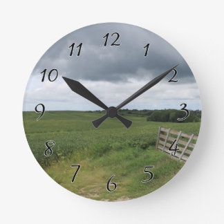 fence gate in front of field with mowed horseshoe round clock