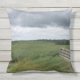 fence gate in front of field with mowed horseshoe throw pillow