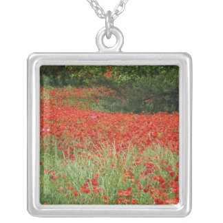 Field of hybrid poppy flowers planted along square pendant necklace