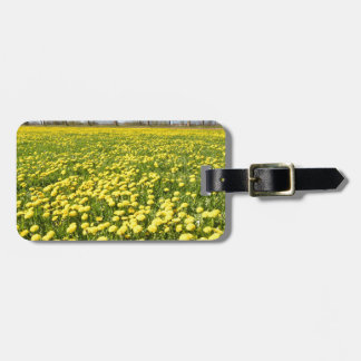Field of yellow dandelions in grass with tree line luggage tag