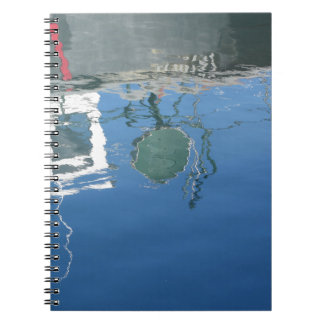 Fishing boat reflects in the water notebook